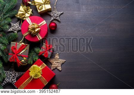 Christmas decoration, gift boxes on dark wooden table. Christmas or New Year holiday background shows the magic of Christmas holiday. Top view.