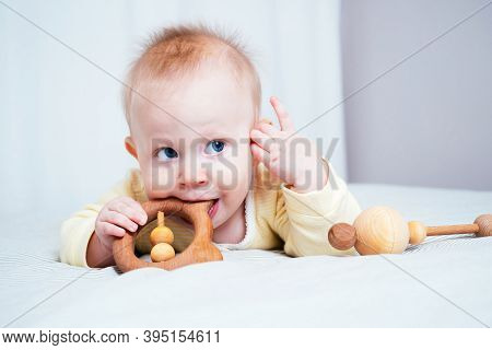 A Seven-month-old Girl With Blue Eyes Lies On Her Stomach In A Bright Room And Nibbles On A Wooden T