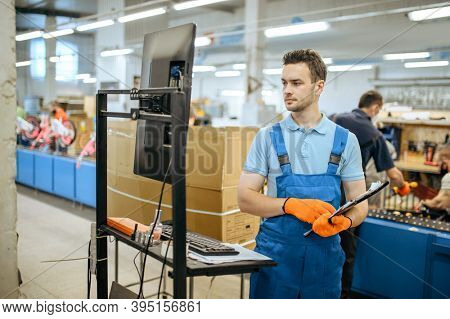 Bicycle factory, worker poses at assembly line