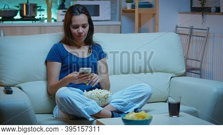 Woman Scrolling On Phone Eating Popcorn And Watching A Movie. Lonely Amused Happy Lady Reading, Writ