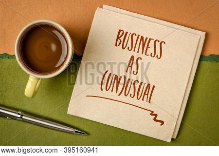 business as unusual note- handwriting on a napkin with coffee, new normal and coronavirus pandemic concept