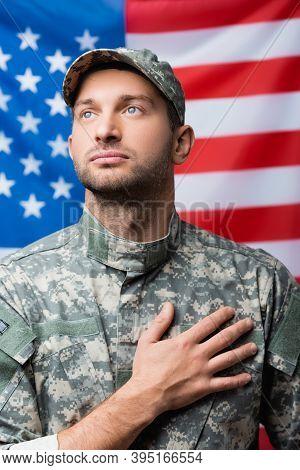 Military Man Pledging Allegiance Near American Flag On Blurred Background