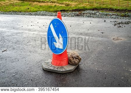 Traffic Cones With White Arrow On Blue Ground Showing Direction At Roadworks