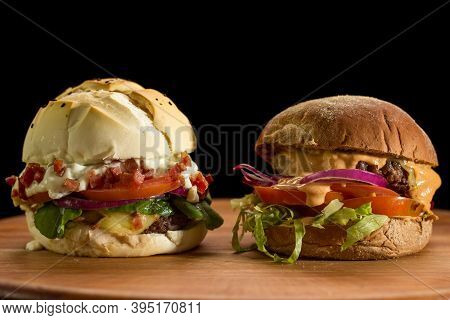 Close Up Of A Homemade Burger On A Chopping Wood Board, On Black Background