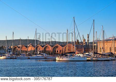 Sunrise In Old Venetian Port, Chania, Crete, Greece. Sailing Boats, Yachts, Pier, Old Venetian Shipy