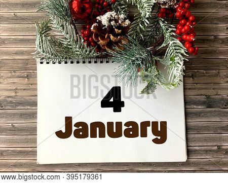 January 4 On A White Notepad.nearby Fir Branches, Red Berries And Cones On A Wooden Background.begin