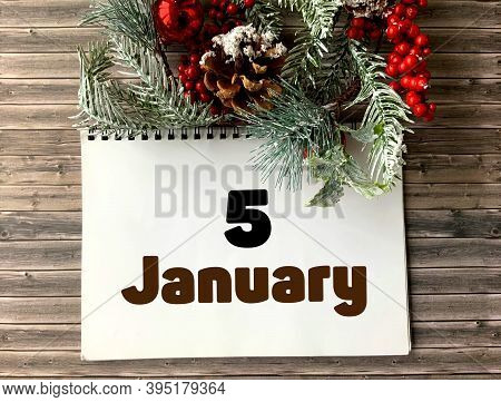 January 5 On A White Notepad.nearby Fir Branches, Red Berries And Cones On A Wooden Background.begin