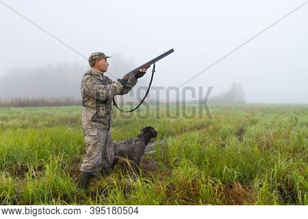 A Hunter And Hunting Dog Are In A Wetlands On A Foggy Morning In Anticipation Of The Hunt
