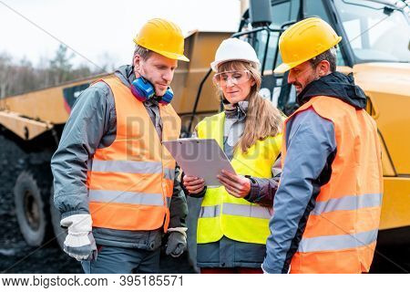 Three workers in a quarry discussing in front of heavy machinery looking at plan