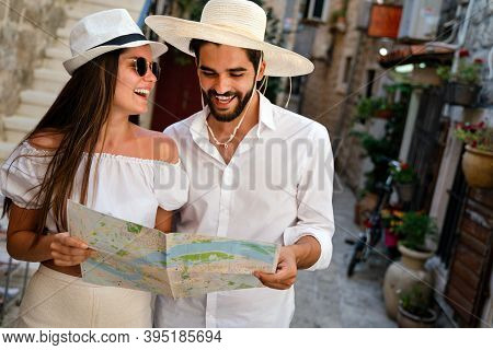 Happy Tourists Couple In Love Sightseeing City With Map During Summer Vacation