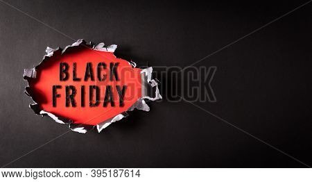 Top View Of Black Torn Paper And The Text Black Friday On Back And Red Background. Black Friday Comp