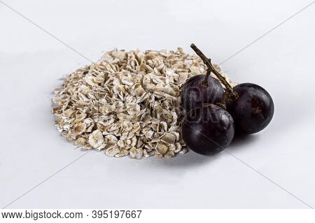 Raw Oatmeal On An Isolated On White Background. Side View Of Raw Dry Rolled Oatmeal With Grapes