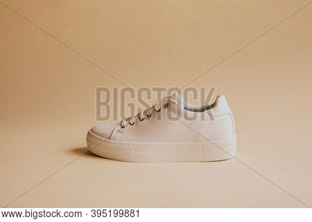 Single white canvas sneakers on beige