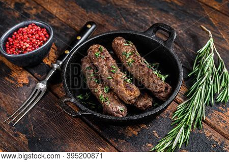 Grilled Mince Meat Sausages In A Pan. Dark Wooden Background. Top View