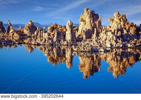 Lime-tuff towers of bizarre shapes rise from the bottom of the lake. The natural wonder of the world is Lake Mono. Magic reflections of tuff outliers in lake water. Magic sunrise on the lake.