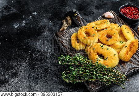 Deep Fried Squid Calamari Rings Breaded On A Cutting Board. Black Background. Top View. Copy Space