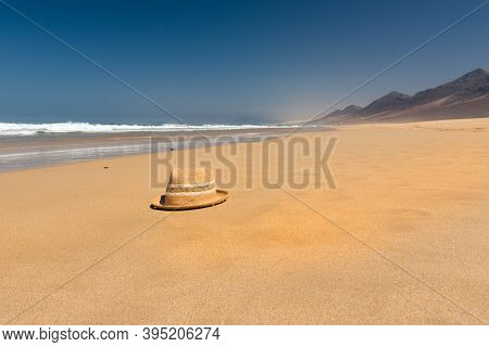 Hat On The Virgin Beaches On The Island Of Fuerteventura. Cofete Beach On The Island Of Fuerteventur