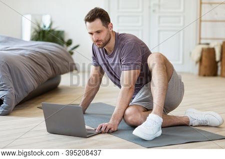 Sporty Man With Laptop Sitting On Gymnastics Mat Ready For Online Training Workout Indoors. Fitness