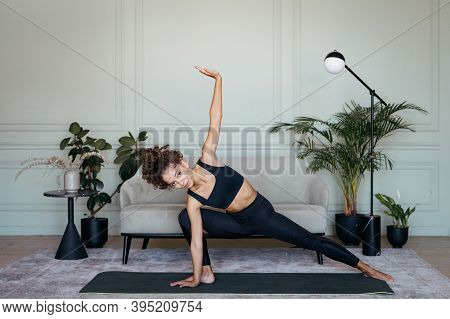 Hatha Yoga Concept. Confident Young Athletic Afro American Woman Making Sport Exercise On Mat, Stret
