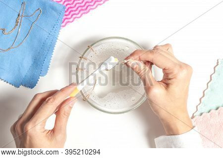 Woman Hands Cleaning Golden Jewelry At Home. Top View