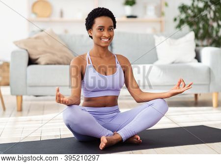 Smiling Black Woman In Sportswear Sitting On Yoga Mat In Lotus Pose And Meditating Or Doing Breathin