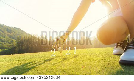Golfer Woman Putting Golf Ball For Happy New Year 2021 On The Green Golf For New Healthy.  Copy Spac