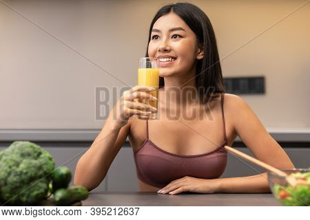 Detox Diet. Excited Slim Asian Woman Drinking Orange Juice Cooking Healthy Vegetable Dinner For Weig