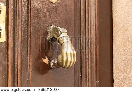 Decorative Copper Handle In The Form Of A Human Hand On The Outer Door Of A Building On The Via Dolo