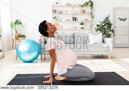 Side View Of Black Pregnant Woman Doing Backbend During Meditation Or Yoga At Home. Beautiful Africa