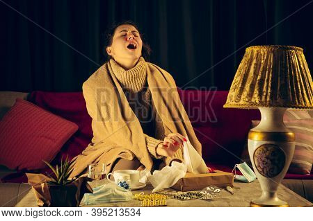 Sneeze. Young Woman Wrapped In A Plaid Looks Sick, Ill, Sneezing And Coughing Sitting On Sofa At Hom