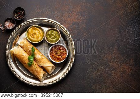 Traditional Indian Rice Pancakes Dosa With Different Dips Chutney, On Rustic Metal Plate On Dark Bro
