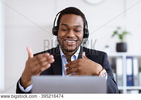 Happy Black Businessman With Headset Having Online Conference, Office Interior, Empty Space. Cheerfu