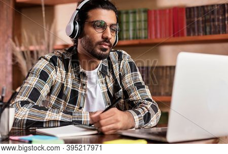 Arab Student Guy Learning Online At Laptop Computer Studying Sitting In Library Near Bookshelf In Un