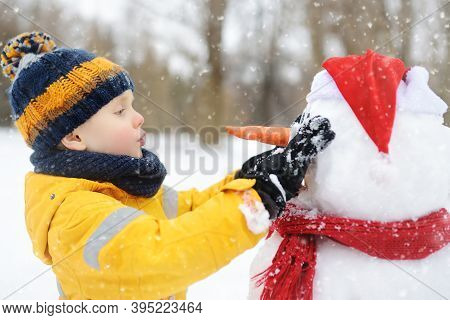 Little Boy Building Funny Snowman. ?hild Attaches Carrot Nose To Snowman In Snowy Park. Active Outdo