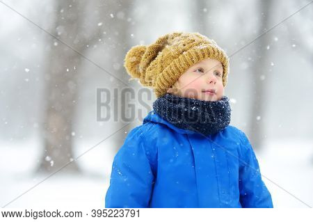 Portrait Of Funny Little Boy In Blue Winter Clothes Walks During A Snowfall. Baby Having Fun While B