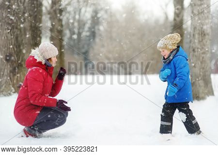 Little Boy And His Mother Having Fun Playing With Fresh Snow. Snow Fight. People Dressed In Warm Clo