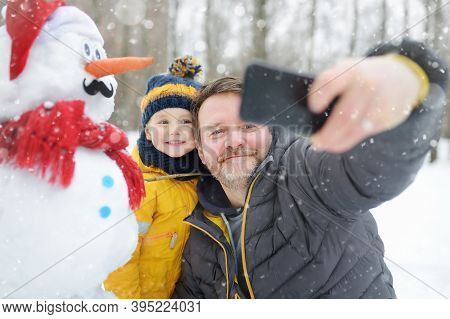 Little Boy And His Father Taking Selfie On Background Of Snowman In Snowy Park. Active Outdoors Leis