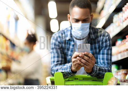 Black Man With Smartphone Shopping In Supermarket. African Guy Buying Food Wearing Face Mask And Usi