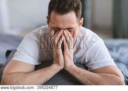Bad Sleep. Guy Rubbing Eyes Waking Up Sleepy In The Morning Lying On Stomach In Bed In Bedroom At Ho