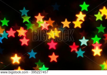 Christmas background. Blurred Christmas bokeh background, festive Christmas multicolor bokeh background. Holiday Christmas glowing color lights with stars, blurred bright abstract bokeh