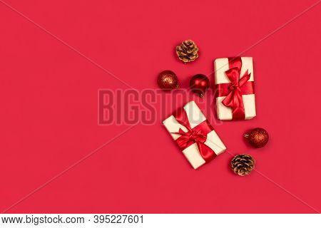 Gifts, Fir Cones, Red Decorations Flat Lay On Red Background Top View, Copy Space. Creative Christma