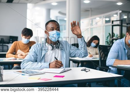 Education During Pandemic Concept. Portrait Of Black Guy Student Raising Hand For Answer Or Asking Q