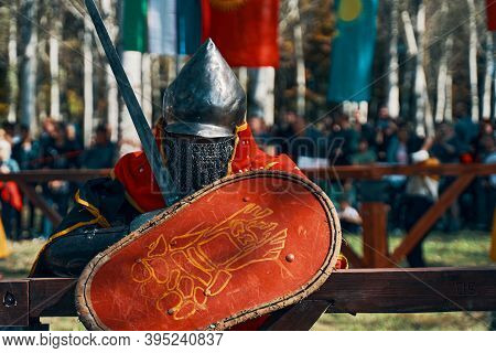 Knight In Armor With A Shield And A Sword. Reconstruction Of Medieval Battles During The Festival Of