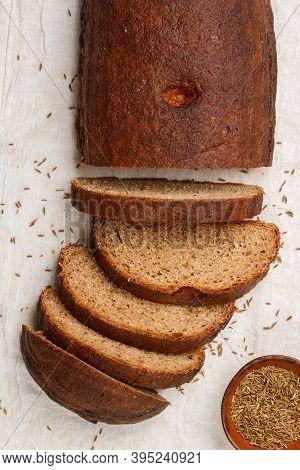 Freshly Baked Homemade Sliced Loaf Of Rye Bread With Cumin  (caraway) On A White Wooden Background.