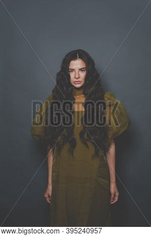 Fashion Portrait Of Beautiful Woman With Long Curly Hair In Green Tulle Dress Posing On Black Backgr