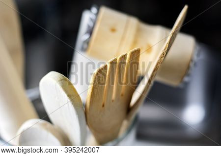 Close-up View Of A Group Of Wooden Kitchen Utensils. Selective Focus On The Fork. Tools For Cooking