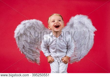 Angel Child Boy With White Wings Laughing. Excited Angelic Children Is Laugh. Cute Excited Kid With