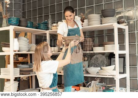 Woman With Ceramic Pottery. Attractive Skilled Young Lady In Apron Standing At Rack With Dishes. Con