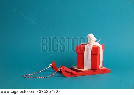 Red Gift Box With A Ribbon On The Sledge Isolated On Ble Background. Christmas Concept. Image Contai