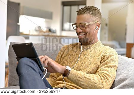 Young trendy afro-amercian guy relaxing in sofa watching movie on digital tablet